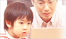 The photo of a boy and his father who are looking at the screen of pc.